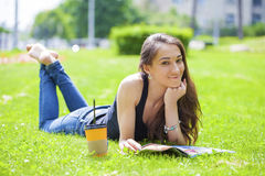 Young beautiful woman sitting in the summer park Royalty Free Stock Photo