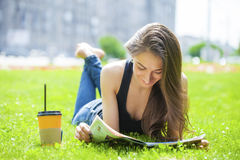 Young beautiful woman sitting in the summer park Royalty Free Stock Photography