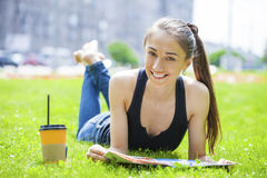 Young beautiful woman sitting in the summer park Stock Images