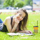 Young beautiful woman sitting in the summer park Stock Photo