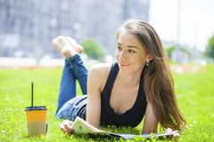 Young beautiful woman sitting in the summer park Royalty Free Stock Photos