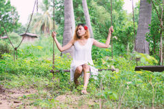 Young beautiful woman sitting on swing with sadness. Woman sitting on swing with sadness Stock Photo