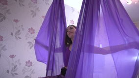 Young beautiful woman sitting and swinging in purple hammock stock video footage