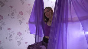 Young beautiful woman sitting and swinging in purple hammock stock video