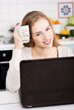 Young beautiful woman sitting by the table with laptop and cup. Stock Image