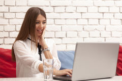 Young beautiful woman sitting at the table and looking at laptop stock photo