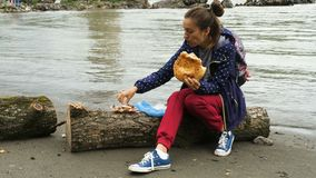 Lunch on the bank of the river. Young beautiful woman sitting on a trunk at the bank of the river and has lunch with meat and bread stock video