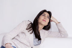 Young beautiful woman sitting on a white sofa and dreaming Royalty Free Stock Photography