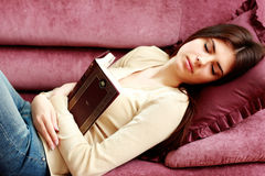 Young beautiful woman sleeping with book on the sofa royalty free stock photography