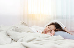 Young beautiful woman sleeping her bed and relaxing Stock Photos