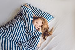 Young beautiful woman sleeping in her bed and relaxing in the mo. Rning Royalty Free Stock Photos