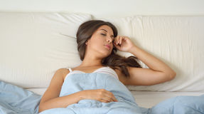 Young beautiful woman sleeping in her bed and relaxing in the morning Royalty Free Stock Photography