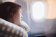 Young beautiful woman sleeping on neck cushion in airplane. Young beautiful woman traveling by plane. A female passenger sleeping on neck cushion in airplane stock photos