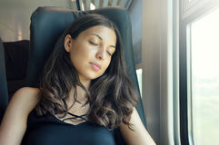Young beautiful woman sleeping sitting in the train. Train passenger traveling sitting in a seat and sleeping.  royalty free stock photo