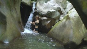 Young beautiful woman in slow motion puts her hands under the stream of small waterfall in mountain lake in green stock video footage
