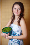 Young beautiful woman with small plant in flowerpo Stock Photography