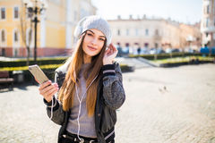 Young beautiful woman with smart phone listening music in the city Royalty Free Stock Images