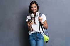 Young beautiful woman with smart phone. Smiling student girl going on a travel. Isolated on gray background. Young beautiful woman with smart phone. Smiling stock photography