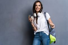 Young beautiful woman with smart phone. Smiling student girl going on a travel. Isolated on gray background. Young beautiful woman with smart phone. Smiling stock image