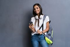 Young beautiful woman with smart phone. Smiling student girl going on a travel. Isolated on gray background. Young beautiful woman with smart phone. Smiling royalty free stock images