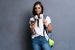 Young beautiful woman with smart phone. Smiling student girl going on a travel. Isolated on gray background. Young beautiful woman with smart phone. Smiling stock photos