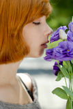 Young beautiful woman smelling purple chinese rose Royalty Free Stock Photos