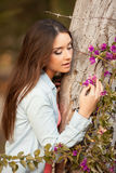 Young beautiful woman smells flowers Royalty Free Stock Image