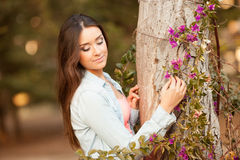 Young beautiful woman smells flowers Royalty Free Stock Photos