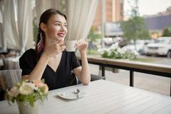 Young beautiful woman with a smile sits on the street and drinks coffee. Summer bright cafe stock photo