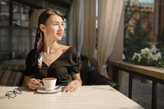 Young beautiful woman with a smile sits on the street and drinks coffee. Summer bright cafe stock images
