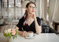 Young beautiful woman with a smile sits on the street and drinks coffee. Summer bright cafe stock photos