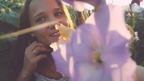 Young beautiful woman smiles and hides in flowers outdoor at sunset through the sun in slow motion with lense flare. Young beautiful woman in flowers outdoor at stock video