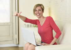 Young beautiful woman smiling happy working at home with laptop computer on sofa couch Royalty Free Stock Image