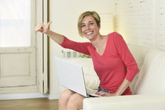 Young beautiful woman smiling happy working at home with laptop computer on sofa couch Royalty Free Stock Images