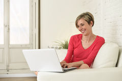 Young beautiful woman smiling happy working at home with laptop computer on sofa couch Royalty Free Stock Photography