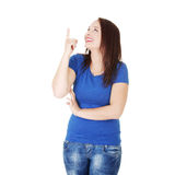 Young beautiful woman is smiling and pointing up. Young beautiful woman wearing blue t-shirt is laughing and pointing up. Isolated on the white background Royalty Free Stock Image