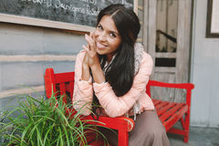Young beautiful woman smiling sitting at red bench Royalty Free Stock Image