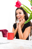 Young beautiful woman smiling while using a Laptop at home Royalty Free Stock Image