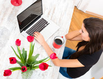 Young beautiful woman smiling while using a Laptop at home Royalty Free Stock Images