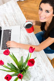 Young beautiful woman smiling while using a Laptop at home Royalty Free Stock Photo