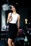 Young, beautiful woman smokes a hookah in cafe. Stock Photo