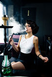 Young, beautiful woman smokes a hookah in cafe. Royalty Free Stock Photos