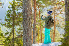 Young beautiful woman with snowshoes and mobile phone chill out Royalty Free Stock Photo