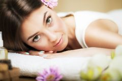 Portrait of a beautiful girl in a spa. Gentle look. Flowers in hair. Aroma oil. Massage cabinet. The concept of health and beauty. Royalty Free Stock Photo
