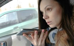 Young beautiful woman speak a voice message on a mobile phone sitting in the car. Young beautiful woman speak a voice message on a mobile phone sitting in the stock images