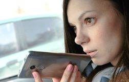 Young beautiful woman speak a voice message on a mobile phone sitting in the car and smiles. Young beautiful woman speak a voice message on a mobile phone royalty free stock image