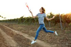 Young beautiful woman spilling wine at vineyard. On sunny day royalty free stock image