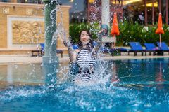 Young woman splashing water in swimming pool Royalty Free Stock Images