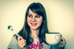 Young beautiful woman with spoon and cup of tea in hands Stock Photo