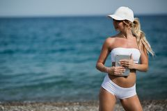 Young beautiful woman in sport suit is using her tablet on the beach.  Stock Images